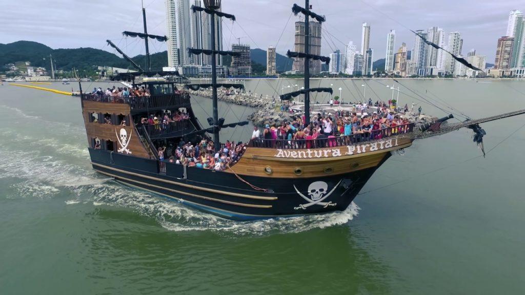 Perto da praia, mas sem ficar parado na areia, apenas tomando sol está o Barco Pirata