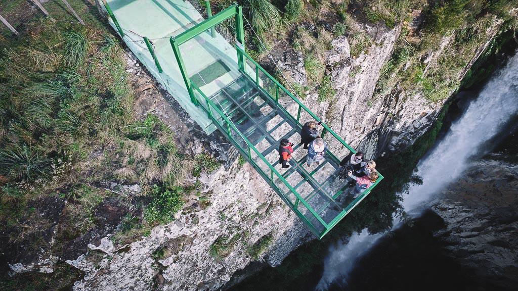 A estrutura de aço e vidro adentram no cânion onde corre um rio lá embaixo